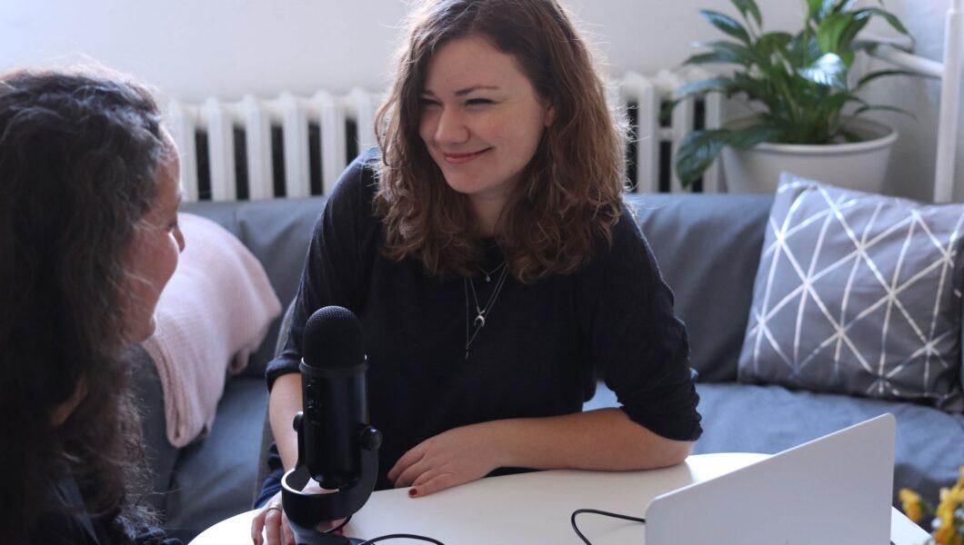 uśmiechnięta kobieta siedzi przodem do obiektywu, przed nią stoi mikrofon);