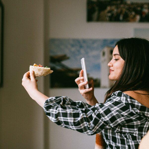 influencerka robiąca zdjęcie pizzy telefonem);
