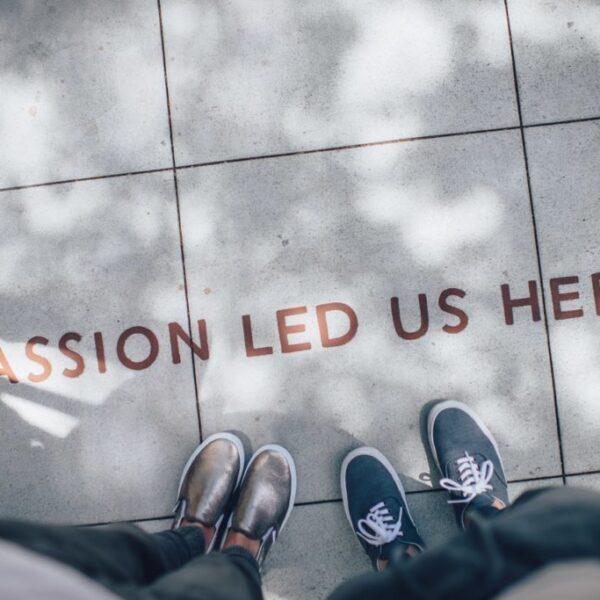 zdjęcie nóg na chodniku, na którym jest napisane passion led us here);