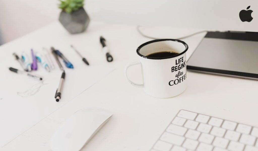 zdjęcie białego biurka a na nim białego kubka, białej myszki i białej klawiatury);