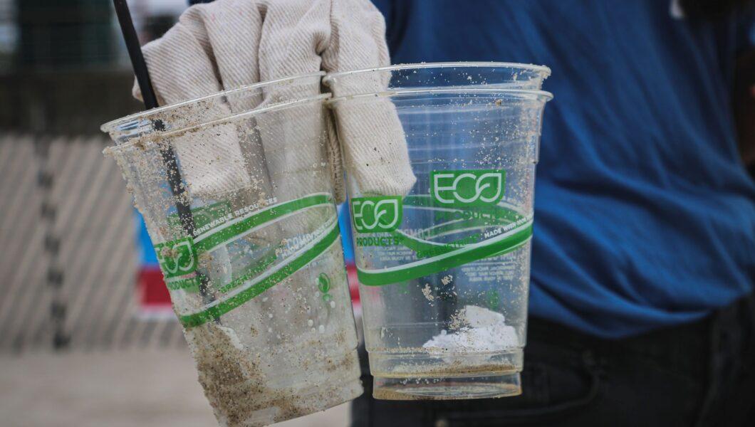ręka trzymająca ubrudzone i opiaszczone plastikowe kubeczki jednorazowe z napisem eco);