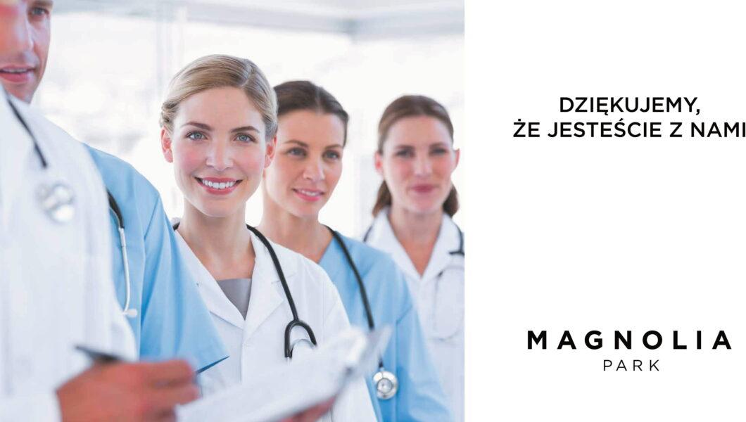 billboard magnolia park, po lewej stronie 4 osoby w lekarskich kitlach, po prawej napis);