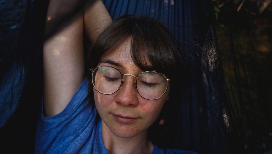 dziewczyna leży na hamaku, nie ma makijażu);