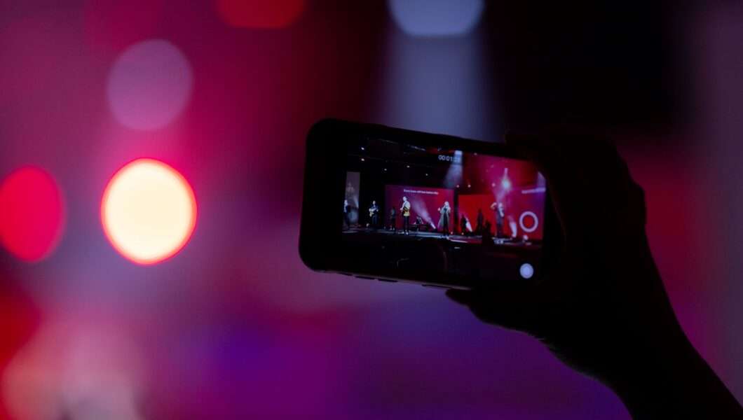 ciemne zdjęcie ręki trzymającej komórkę i kręcącej live z koncertu);