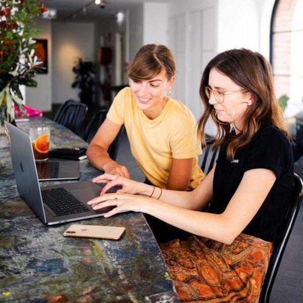 dwie kobiety wspólnie patrzące w jeden laptop, siedzą w białym wnętrzu);